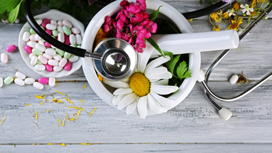 Flowers and medicine in a mortar and pestle representing Alternative Medicine in Downers Grove IL