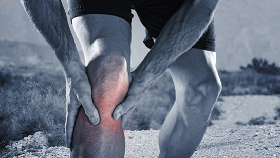 Runner holding knee in pain requiring Natural Remedies for Joint Pain in Clarendon Hills IL