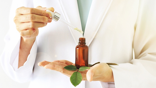 Natural Medicine Doctor in Clarendon Hills IL holding a vial essential oils