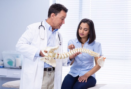 A Chiropractor in Westmont IL showing a patient a model of the spine