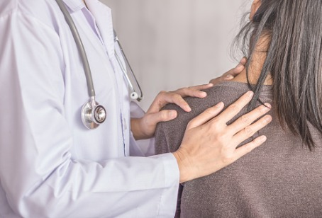 Chiropractor in Hinsdale IL feeling a patients shoulder and upper back