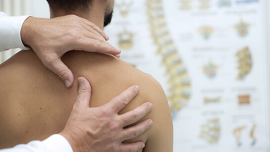 A chiropractor in Downers Grove IL performing chiropractic care on a young adult